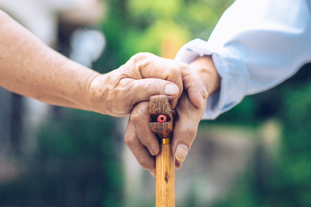 Elder holding hands and stick SansiriBlog 1